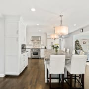 A kitchen with dark wood floors, white cabinets, simple and clean stainless steel finishes. The large island has white full-back seating for 6, and a black with white swirls marble counter-top.